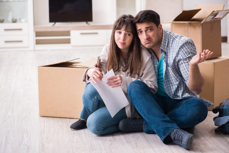 A man and a woman sit on the floor of an apartment with moving boxes open in the background while making sad faces. The woman is holding an illegible letter, which is presumably the cause of their sad faces.