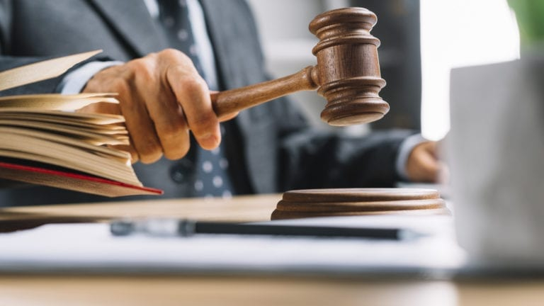This is a picture of a man's torso and arms, shown in a business suit in the process of banging a legal judge's gavel onto its base, with an open text book next to him.